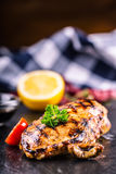 Grilled chicken breast in different variations with cherry tomatoes,  mushrooms, herbs, cut lemon on a wooden board or teflon pan. Stock Image