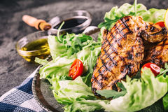 Grilled chicken breast in different variations with cherry tomatoes,  mushrooms, herbs, cut lemon on a wooden board or teflon pan. Stock Images