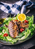 Grilled chicken breast in different variations with cherry tomatoes,  mushrooms, herbs, cut lemon on a wooden board or teflon pan. Royalty Free Stock Image