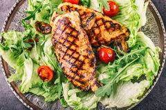 Grilled chicken breast in different variations with lettuce salad cherry tomatoes  mushrooms herbs cut lemon on a wooden board or Royalty Free Stock Photo