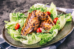Grilled chicken breast in different variations with lettuce salad cherry tomatoes  mushrooms herbs cut lemon on a wooden board or Royalty Free Stock Images