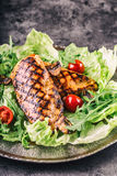 Grilled chicken breast in different variations with lettuce salad cherry tomatoes  mushrooms herbs cut lemon on a wooden board or Stock Image