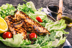 Grilled chicken breast in different variations with lettuce salad cherry tomatoes  mushrooms herbs cut lemon on a wooden board or Stock Images
