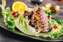 Grilled chicken breast in different variations with lettuce salad cherry tomatoes  mushrooms herbs cut lemon on a wooden board or Stock Photography
