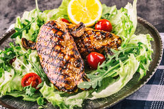 Grilled chicken breast in different variations with lettuce salad cherry tomatoes  mushrooms herbs cut lemon on a wooden board or Stock Photos