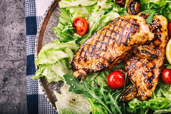 Grilled chicken breast in different variations with lettuce salad cherry tomatoes  mushrooms herbs cut lemon on a wooden board or Royalty Free Stock Photography