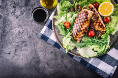 Grilled chicken breast in different variations with lettuce salad cherry tomatoes  mushrooms herbs cut lemon on a wooden board or Royalty Free Stock Image