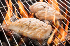 Grilled chicken breast on the flaming grill.  Royalty Free Stock Photos