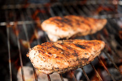Grilled chicken breast on the flaming grill royalty free stock photo