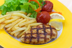 Grilled chicken breast with french fries ,baked to Stock Photography