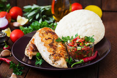 Grilled chicken breast with fresh tomato salsa and pita. stock image