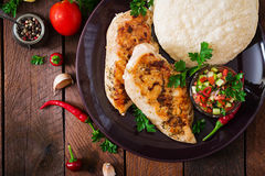 Grilled chicken breast with fresh tomato salsa and pita. royalty free stock image