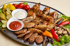 Grilled chicken breast with mushrooms. Cold meats with mushrooms and vegetables on a large platter Stock Images
