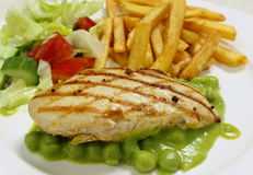 Grilled chicken breast on pea puree side view Royalty Free Stock Photo