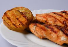 Grilled chicken breast. With grilled potatoes on a white plate. Detail.n Royalty Free Stock Images
