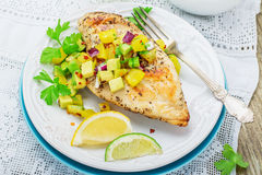Grilled chicken breast with salsa pineapple. Avocado and sweet red onion, parsley and cilantro. Posted on a white plate on the table with a white lace vintage royalty free stock photo