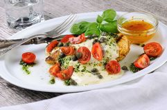 Grilled chicken breast topped with melted mozzarella cheese, basil pesto, tomato ,caper. Grilled chicken breast topped with melted mozzarella cheese, basil pesto stock photos