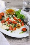 Grilled chicken breast topped with melted mozzarella cheese, basil pesto, tomato and caper stock image