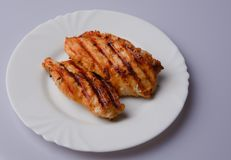 Grilled chicken breast. Two pieces on a white plate Stock Photography