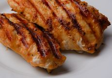 Grilled chicken breast. Two pieces on a white plate. Detail Stock Photos