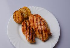 Grilled chicken breast. Two pieces on a white plate. General view from the top Stock Images