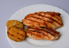 Grilled chicken breast. Two pieces on a white plate with grilled potatoes Stock Photo