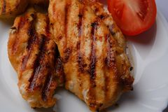 Grilled chicken breast. Two pieces on a white plate with grilled potatoes and tomatoes Royalty Free Stock Photography