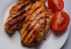 Grilled chicken breast. Two pieces on a white plate with grilled potatoes and tomatoes Stock Image