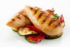 Grilled chicken breast with zucchini and capsicum. A close up of a gourmet dish with grilled chicken breast, zucchini and capsicum on a white background with Stock Images