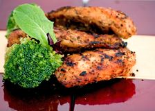 Grilled Chicken Breasts. On red and tan reflective tiles.  Includes green vegetables to complete the meal Royalty Free Stock Images