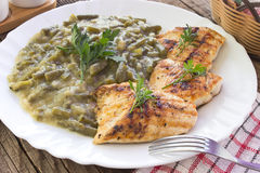 Grilled chicken breasts with cooked green beans in plate on tabl Stock Image
