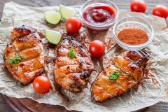 Grilled chicken breasts in hot mango sauce. On the baking paper Royalty Free Stock Image