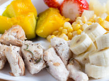 Grilled chicken breasts with pumpkin, corn, banana and strawberr. Y on a white dish plate Stock Photos