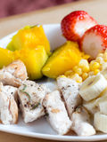 Grilled chicken breasts with pumpkin, corn, banana and strawberr. Y on a white dish plate Stock Image