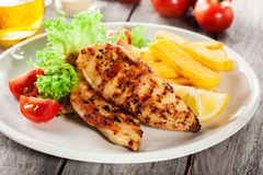 Grilled chicken breasts served with fries and fresh salad Stock Photos
