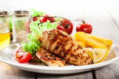 Grilled chicken breasts served with fries and fresh salad. On a plate Royalty Free Stock Images
