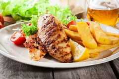 Grilled chicken breasts served with fries and fresh salad. On a plate Royalty Free Stock Photo