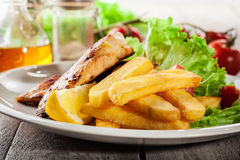 Grilled chicken breasts served with fries and fresh salad Royalty Free Stock Photos