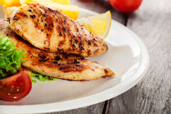 Grilled chicken breasts served with fries and fresh salad. On a plate Stock Image