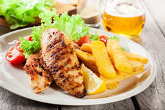 Grilled chicken breasts served with fries and fresh salad. On a plate Stock Photos