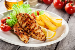Grilled chicken breasts served with fries and fresh salad. On a plate Royalty Free Stock Photos