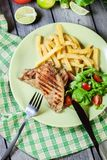 Grilled chicken breasts served with fries. And fresh salad on a plate Royalty Free Stock Photo