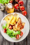 Grilled chicken breasts served with fries and fresh salad. On a plate. Top view Royalty Free Stock Photography
