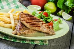 Grilled chicken breasts served with fries. And fresh salad on a plate Stock Image