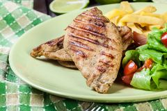 Grilled chicken breasts served with fries. And fresh salad on a plate Stock Photography