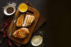 Grilled chicken breasts with spices on wooden desk. Top view. Space for copy. Toned image Royalty Free Stock Photos