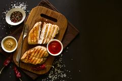 Grilled chicken breasts with spices on wooden desk. Top view. Space for copy. Toned image Stock Images