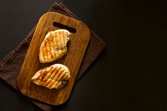 Grilled chicken breasts with spices on wooden desk Royalty Free Stock Image