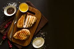 Grilled chicken breasts with spices on wooden desk. Top view. Space for copy. Toned image Stock Photography