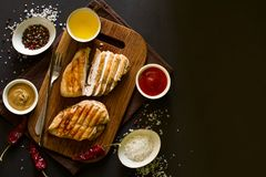 Grilled chicken breasts with spices on wooden desk. Top view. Space for copy. Toned image Stock Image